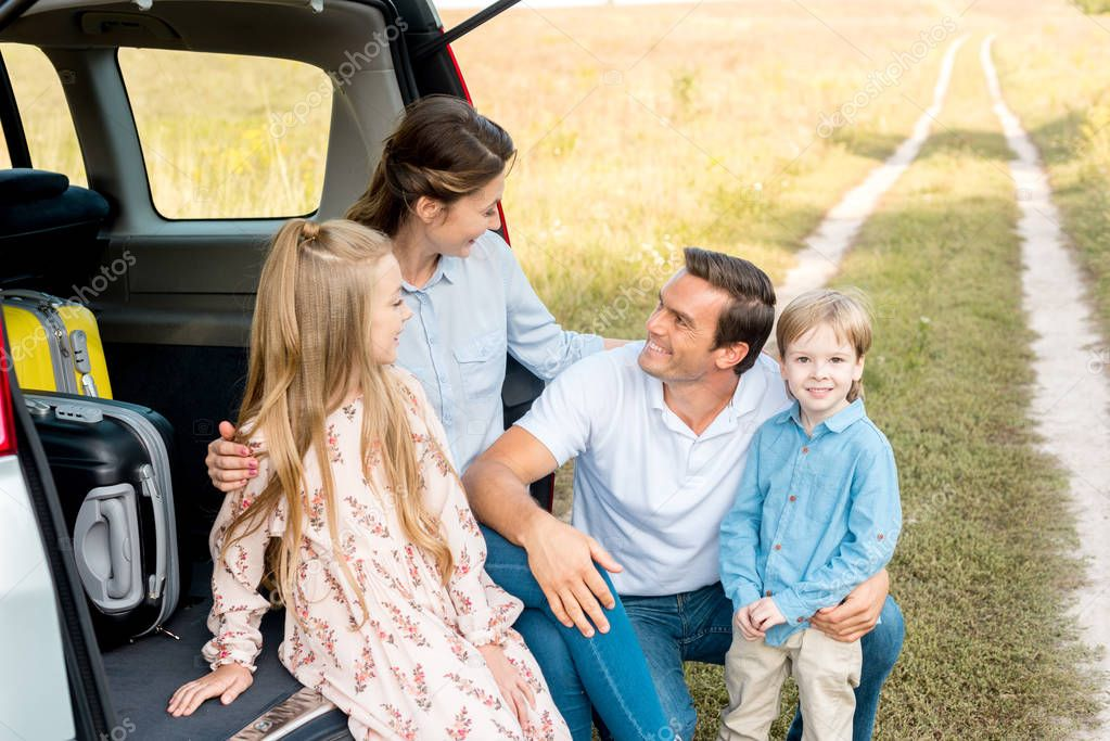 beautiful young family sitting in car trunk and embracing in field while having car trip