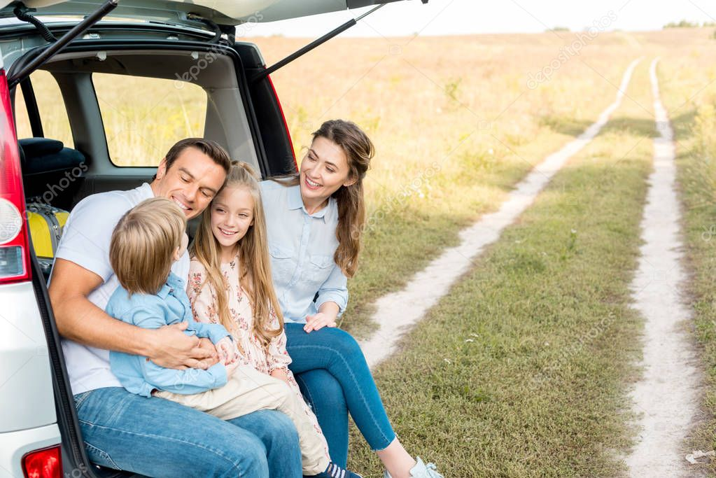 beautiful young family spending time together in field while having car trip