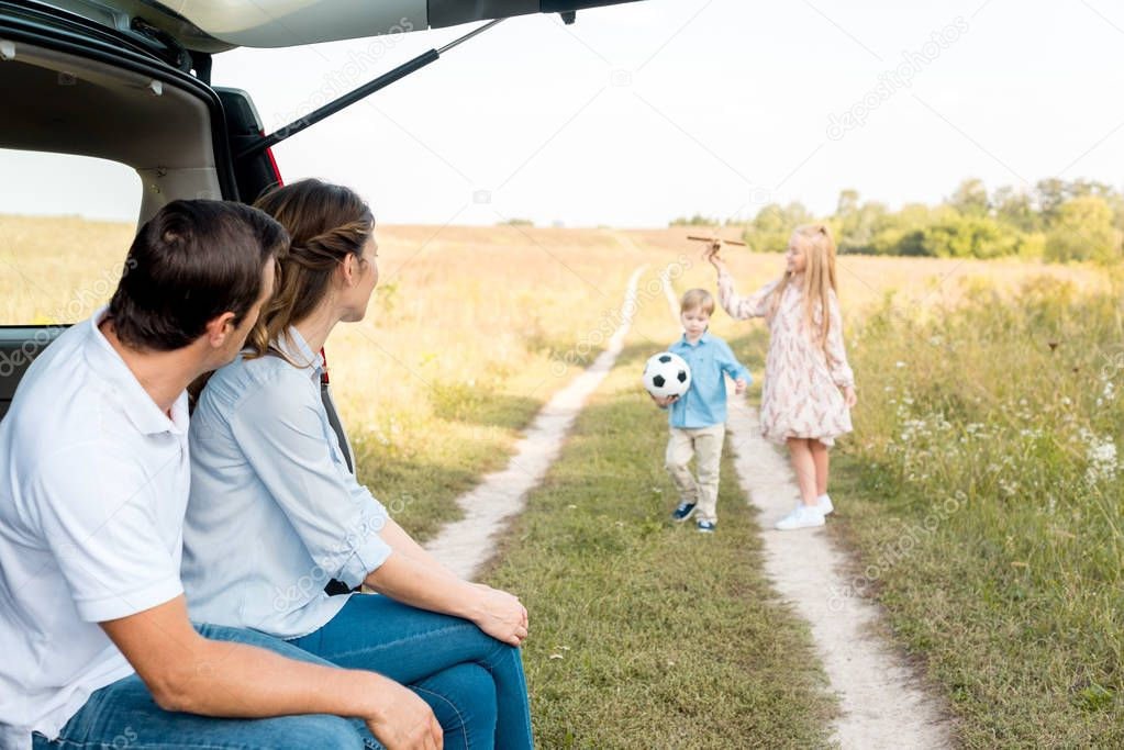 young family spending time together in field while travelling by car
