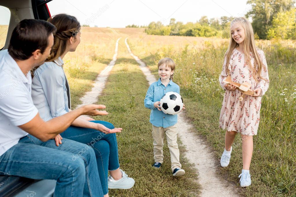 beautiful young family spending time together in field while travelling by car