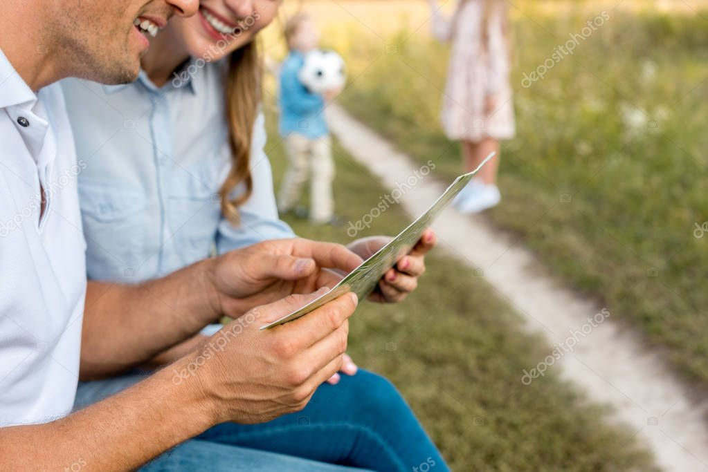 happy young couple looking at map while kids playing football in field