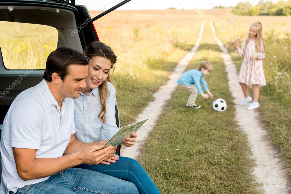 happy young family spending time together in field while travelling by car
