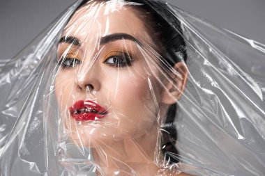 beautiful young woman with transparent polyethylene on face looking at camera on grey