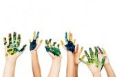 Fotografia ritagliata colpo dei bambini che mostrano le mani in vernice variopinta isolata su bianco