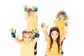 vysoký úhel pohledu šťastných dětí znázorňující ruce v programu Malování a usmívá se na kameru izolované na bílém