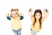 Fotografie vysoký úhel pohledu rozkošné děti zobrazuje barevné malované rukou a usmívá se na kameru izolované na bílém