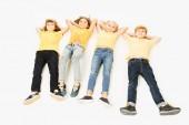vysoký úhel pohledu rozkošný šťastné děti ve žlutých tričkách leží vedle sebe a usmívá se na kameru izolované na bílém