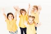 pohled z vysokého úhlu skupiny šťastných dětí, ukazuje rukou a usmívá se na kameru izolované na bílém