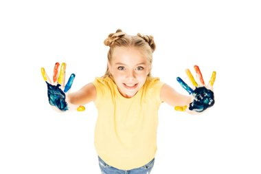 high angle view of beautiful happy child showing colorful painted hands and smiling at camera isolated on white