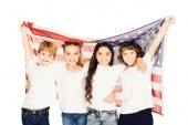 smiling adorable children standing under american flag and looking at camera isolated on white