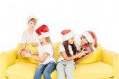 adorable kids in santa hats sitting on yellow sofa with gift boxes isolated on white
