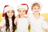 Fotografie portrait of smiling adorable kids in santa hats sitting on yellow sofa and looking at camera isolated on white