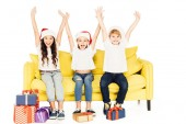 Fotografie happy adorable kids in santa hats sitting on yellow sofa with raised hands isolated on white