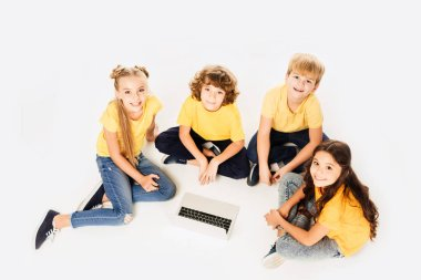 high angle view of happy kids using laptop and smiling at camera isolated on white
