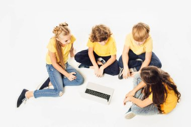 high angle view of group of cute children sitting and using laptop together isolated on white