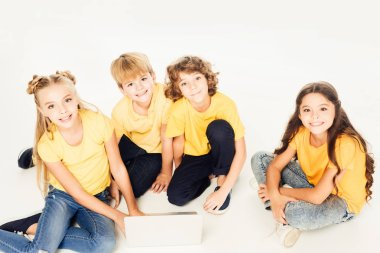 high angle view of adorable kids using laptop and smiling at camera isolated on white