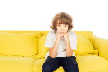 upset boy sitting on yellow sofa and resting chin on hands isolated on white, looking at camera