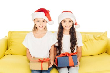 smiling adorable kids in santa hats sitting on yellow sofa with presents isolated on white