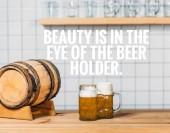 selektiver Fokus auf Bierfass und zwei Krüge mit hellem Bier an der Theke mit dem Schriftzug Schönheit liegt im Auge des Bierhalters