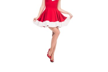 cropped image of sexy santa girl in shoes with high heels raising up christmas dress isolated on white