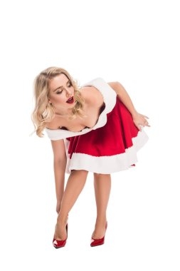 sexy santa girl in christmas dress taking off shoes with high heels isolated on white