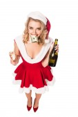 Fotografie high angle view of attractive santa girl in christmas dress with money in mouth holding champagne bottle and glass isolated on white