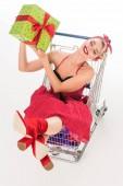 Fotografie Vogelperspektive Anzeigen von attraktiven Frau in Pin-up Kleid sitzt im Warenkorb mit Geschenkbox isoliert auf weiss