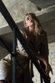 Fotografia Inquadratura dal basso del modello alla moda che propone alla ringhiera