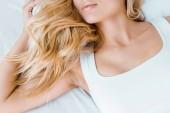 Oříznout záběr mladá blond žena ležela v posteli