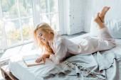 krásná usměvavá dívka v pyžamu ležel na posteli a čtení knihy