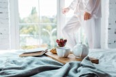 oříznutý obraz ženy, otevírací okna, snídaně a kniha na posteli