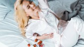 pohled z vysokého úhlu krásné usměvavé ženy v pyžamu ležel s jahodami v posteli ráno