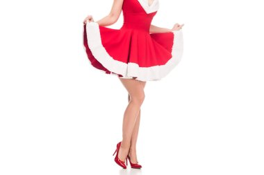 cropped image of sexy santa girl in high heels raising up christmas dress isolated on white