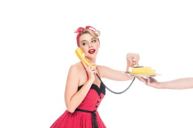 young pin up woman dialing phone number of retro telephone on serving tray in male hand isolated on white
