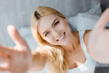 selective focus of happy blonde woman reaching hands and smiling at camera in bedroom