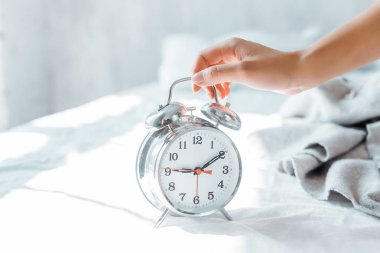 close-up partial view of young woman holding alarm clock in bedroom