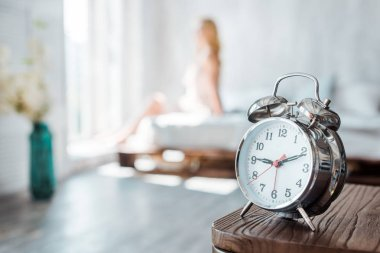 close-up view of alarm clock on wooden table and young woman sitting on bed behind