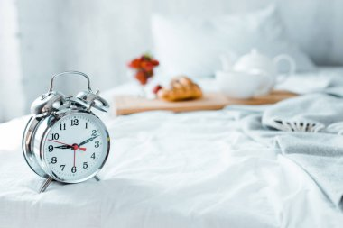 Close-up view of alarm clock and tasty breakfast on bed stock vector