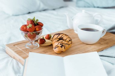 appetizing breakfast of strawberries, croissant and coffee on wooden tray on bed