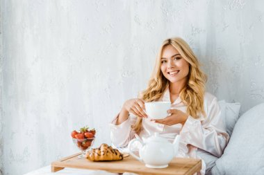 beautiful smiling woman holding cup of tea in bed in morning and looking at camera