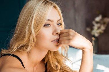 portrait of pensive attractive woman in black lingerie looking away in bedroom