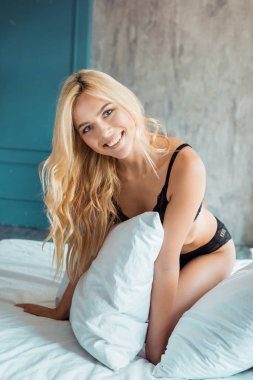 smiling attractive woman in black lingerie looking at camera in bedroom