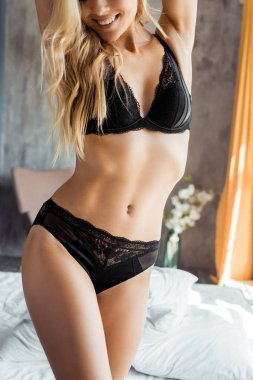 cropped image of attractive smiling woman in black lingerie standing in bedroom