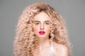 Fotografie Porträt einer attraktiven jungen Frau mit langen lockigen Haaren, die isoliert auf grau in die Kamera blickt