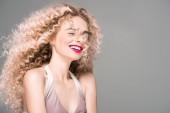 Porträt einer glücklichen jungen Frau mit langen lockigen Haaren, die isoliert auf grau lacht