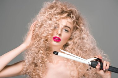 attractive naked girl with long curly hair holding hair curler and looking at camera isolated on grey