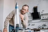 Fotografie handsome engineer modeling rocket and measuring with ruler at home