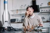 stanco uomo bello giocare a scacchi e toccando naso ponte a casa