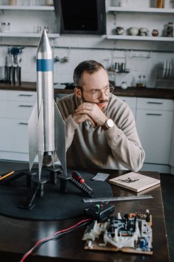 pensive engineer sitting at table with rocket model at home and looking away
