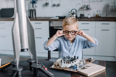 adorable boy touching glasses and looking at circuit board in kitchen on weekend
